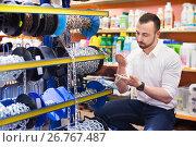 Купить «Man next to showcase with metallic chains», фото № 26767487, снято 20 февраля 2019 г. (c) Яков Филимонов / Фотобанк Лори