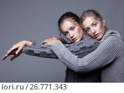 Two young women in gray sweaters on grey background. Beautiful girls stretching hands forward in embrace. Female friendship concept, фото № 26771343, снято 26 июля 2017 г. (c) Serg Zastavkin / Фотобанк Лори