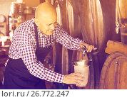 Купить «Elderly man wine maker taking wine from wood», фото № 26772247, снято 30 марта 2020 г. (c) Яков Филимонов / Фотобанк Лори
