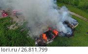 Купить «Горящие деревянные постройки и пожарная команда, приступающая к тушению пожара», видеоролик № 26811799, снято 16 июля 2017 г. (c) Кекяляйнен Андрей / Фотобанк Лори