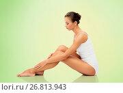 Купить «beautiful woman touching her smooth bare legs», фото № 26813943, снято 9 апреля 2017 г. (c) Syda Productions / Фотобанк Лори