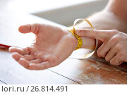 Купить «close up of male hands with tape measuring wrist», фото № 26814491, снято 14 мая 2015 г. (c) Syda Productions / Фотобанк Лори