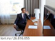 Купить «businessman calling on desk phone at hotel room», фото № 26816055, снято 22 мая 2017 г. (c) Syda Productions / Фотобанк Лори
