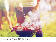 Купить «man cooking meat on barbecue grill at summer party», фото № 26816575, снято 28 августа 2016 г. (c) Syda Productions / Фотобанк Лори