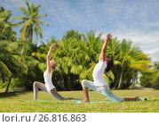 Купить «couple making yoga in low lunge pose outdoors», фото № 26816863, снято 6 августа 2014 г. (c) Syda Productions / Фотобанк Лори