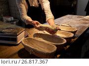 Купить «baker with dough rising in baskets at bakery», фото № 26817367, снято 15 мая 2017 г. (c) Syda Productions / Фотобанк Лори