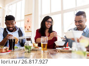 Купить «happy friends eating at restaurant», фото № 26817927, снято 2 мая 2017 г. (c) Syda Productions / Фотобанк Лори