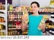 Купить «Woman choosing different oil in bottle», фото № 26837243, снято 6 июня 2017 г. (c) Яков Филимонов / Фотобанк Лори