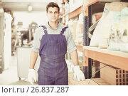 Купить «Portrait of diligent male in uniform on his workplace in building store.», фото № 26837287, снято 26 июля 2017 г. (c) Яков Филимонов / Фотобанк Лори