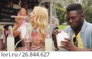 Купить «happy multiracial couple eating wok at food truck», видеоролик № 26844627, снято 17 июля 2019 г. (c) Syda Productions / Фотобанк Лори