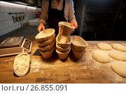 Купить «baker with baskets for dough rising at bakery», фото № 26855091, снято 15 мая 2017 г. (c) Syda Productions / Фотобанк Лори