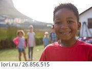 Купить «Portrait of happy boy with friends playing in background», фото № 26856515, снято 25 апреля 2017 г. (c) Wavebreak Media / Фотобанк Лори