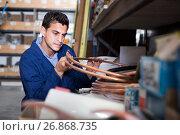 Купить «Man assistant is checking rolls of copper trumpet», фото № 26868735, снято 26 июля 2017 г. (c) Яков Филимонов / Фотобанк Лори