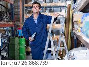 sellerman in uniform is using ladder near shelving. Стоковое фото, фотограф Яков Филимонов / Фотобанк Лори