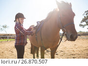 Купить «Girl adjusting saddle on horse in ranch», фото № 26870507, снято 3 мая 2017 г. (c) Wavebreak Media / Фотобанк Лори