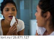 Купить «Young woman wiping face», фото № 26871127, снято 25 мая 2017 г. (c) Wavebreak Media / Фотобанк Лори