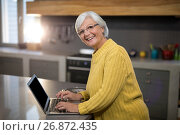 Купить «Smiling senior woman using laptop in kitchen», фото № 26872435, снято 25 мая 2017 г. (c) Wavebreak Media / Фотобанк Лори