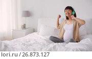 Купить «pregnant asian woman in headphones with smartphone», видеоролик № 26873127, снято 27 июня 2019 г. (c) Syda Productions / Фотобанк Лори