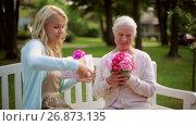 Купить «daughter with flowers and gift for senior mother», видеоролик № 26873135, снято 20 августа 2019 г. (c) Syda Productions / Фотобанк Лори