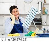Купить «Male cleaner is speaking on the phone instead of cleaning», фото № 26874631, снято 18 мая 2017 г. (c) Яков Филимонов / Фотобанк Лори