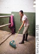 Купить «Female jockey cleaning stable», фото № 26881535, снято 3 мая 2017 г. (c) Wavebreak Media / Фотобанк Лори