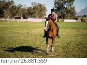 Купить «Full length of female jockey horseback riding on field», фото № 26881559, снято 3 мая 2017 г. (c) Wavebreak Media / Фотобанк Лори