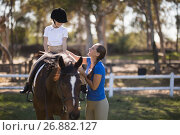 Купить «Side view of happy female jockey teaching girl», фото № 26882127, снято 3 мая 2017 г. (c) Wavebreak Media / Фотобанк Лори