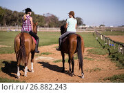 Купить «Rear view of female friends sitting on horse», фото № 26882243, снято 3 мая 2017 г. (c) Wavebreak Media / Фотобанк Лори