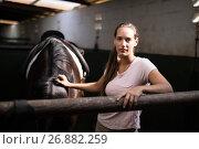 Купить «Portrait of young female jockey standing by horse», фото № 26882259, снято 3 мая 2017 г. (c) Wavebreak Media / Фотобанк Лори
