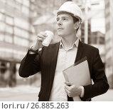 Купить «Professional man in helmet working with documents», фото № 26885263, снято 20 апреля 2017 г. (c) Яков Филимонов / Фотобанк Лори