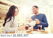Купить «happy couple drinking tea at cafe», фото № 26885307, снято 23 января 2016 г. (c) Syda Productions / Фотобанк Лори