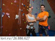 Купить «Portrait of confident athletes standing by climbing wall in gym», фото № 26886627, снято 10 мая 2017 г. (c) Wavebreak Media / Фотобанк Лори