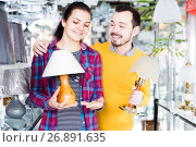 Купить «man and a girl are examining the options for lamps», фото № 26891635, снято 16 февраля 2017 г. (c) Яков Филимонов / Фотобанк Лори