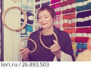 Купить «Senior female choosing embroidery hoops», фото № 26893503, снято 10 мая 2017 г. (c) Яков Филимонов / Фотобанк Лори