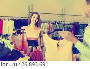 Купить «Couple are examining models of a dress», фото № 26893691, снято 11 апреля 2017 г. (c) Яков Филимонов / Фотобанк Лори