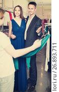 Купить «woman shop assistant offering dress variants to cheerful pair», фото № 26893711, снято 11 апреля 2017 г. (c) Яков Филимонов / Фотобанк Лори
