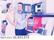 Купить «Young husband and wife are choosing new microwave», фото № 26893819, снято 15 июня 2017 г. (c) Яков Филимонов / Фотобанк Лори