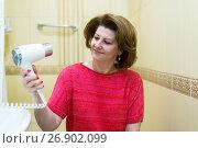 Купить «woman dries hair a hair dryer in a bathroom», фото № 26902099, снято 5 июня 2017 г. (c) Володина Ольга / Фотобанк Лори
