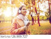 Купить «woman with smartphone and earphones in autumn park», фото № 26909727, снято 6 октября 2016 г. (c) Syda Productions / Фотобанк Лори