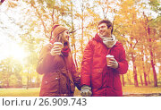 Купить «happy couple with coffee walking in autumn park», фото № 26909743, снято 9 октября 2016 г. (c) Syda Productions / Фотобанк Лори