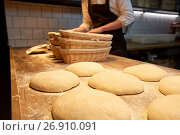 Купить «baker with baskets for dough rising at bakery», фото № 26910091, снято 15 мая 2017 г. (c) Syda Productions / Фотобанк Лори