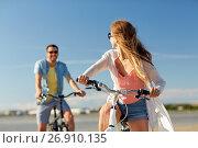 Купить «happy young couple riding bicycles at seaside», фото № 26910135, снято 23 июля 2017 г. (c) Syda Productions / Фотобанк Лори