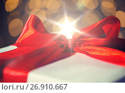 Купить «close up of christmas gift with bow over lights», фото № 26910667, снято 7 октября 2015 г. (c) Syda Productions / Фотобанк Лори