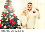 Купить «happy couple decorating christmas tree at home», фото № 26921647, снято 8 октября 2015 г. (c) Syda Productions / Фотобанк Лори