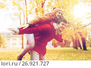 Купить «happy young couple having fun in autumn park», фото № 26921727, снято 9 октября 2016 г. (c) Syda Productions / Фотобанк Лори