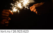 Купить «hands playing with burning sparklers in darkness», видеоролик № 26923623, снято 9 сентября 2017 г. (c) Syda Productions / Фотобанк Лори