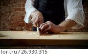 A chef cutting one clove of garlic on wood chopping board for preparing food. 4K. Стоковое видео, видеограф ActionStore / Фотобанк Лори
