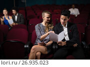 Купить «Couple reading in theatre», фото № 26935023, снято 20 апреля 2017 г. (c) Wavebreak Media / Фотобанк Лори
