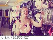 Купить «Happy young wife choosing bra in the underwear», фото № 26936127, снято 13 апреля 2017 г. (c) Яков Филимонов / Фотобанк Лори