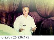 Купить «Positive house sommelier checking quality of red wine», фото № 26936175, снято 22 сентября 2016 г. (c) Яков Филимонов / Фотобанк Лори